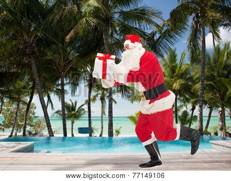 christmas, holidays, travel and people concept - man in costume of santa claus running with gift box over swimming pool on tropical beach background
