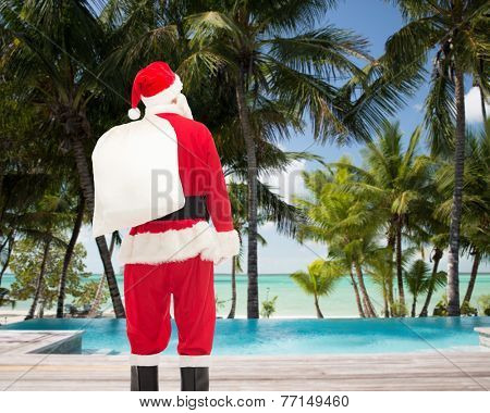 christmas, holidays and people concept - man in costume of santa claus with bag from back over tropical beach and swimming pool background