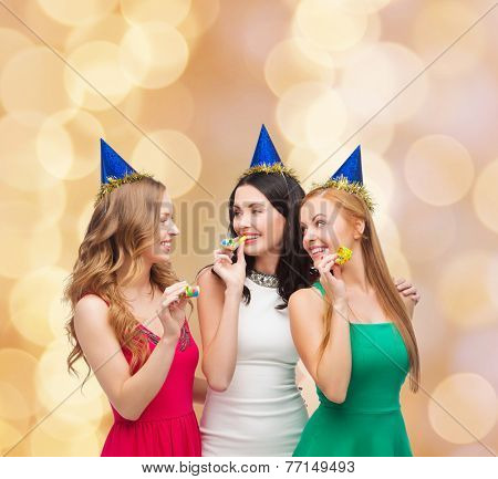 holidays, people and celebration concept - smiling women in party caps blowing to whistles over beige lights background