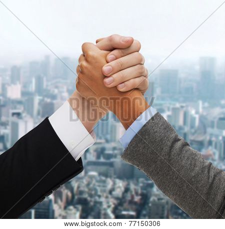 business, people and competition concept - hands of two people armwrestling over green background