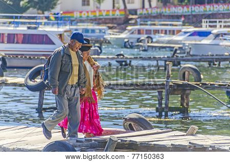 COPACABANA, BOLIVIA, MAY 7, 2014:  Local woman in traditional attire walks with her husband on jetty in port (Titicaca lake)