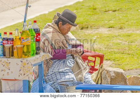 COPACABANA, BOLIVIA, MAY 7, 2014: Local seller of sodas in traditional attire knits while waiting for buyers
