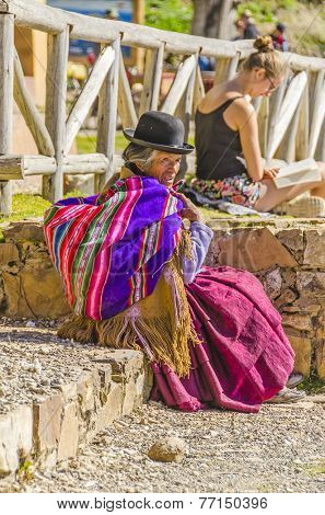 YUMANI (ISLA DEL SOL), BOLIVIA, MAY 7, 2014: Local elderly woman in traditional attire sits outdoors while young tourist tans in skimpy outfit