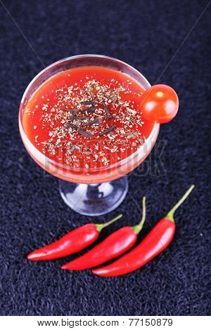 Tomato juice in goblet, chilly pepper and fresh tomatoes on dark background