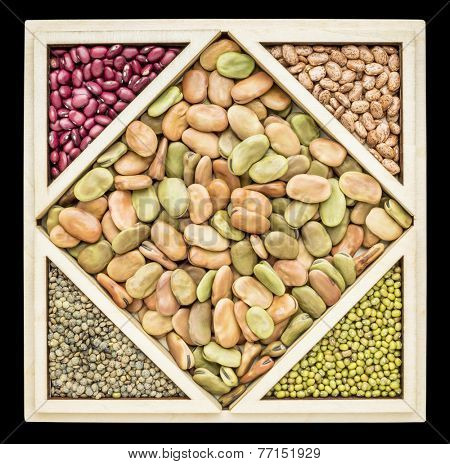 fava beans and other beans and French lentils in a wooden tray inspired by Chinese tangram puzzle, isolated on black
