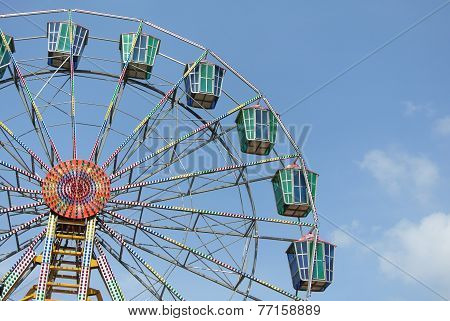 A colourful ferris wheel with blue sky