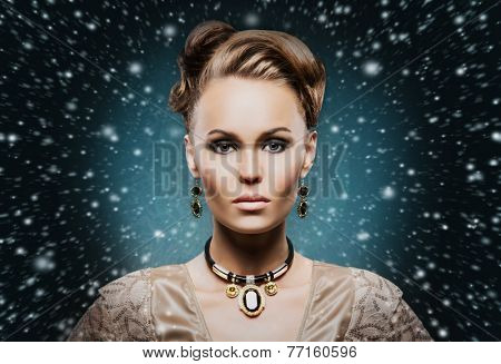 Portrait of young and beautiful woman in a precious necklace and earrings. Christmas background
