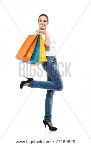 Young, attractive and happy shopping girl with bright shopping bags isolated on white