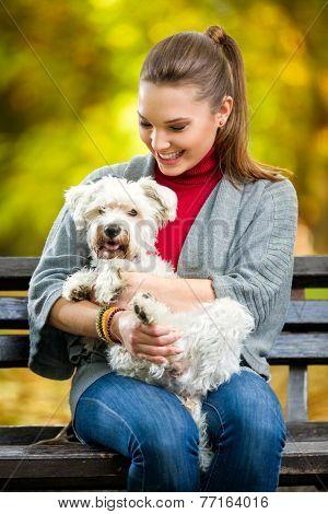 Smiling girl  holding cute maltese dog in park