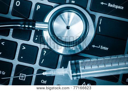 Computer system health - Stethoscope and syringe on a computer keyboard
