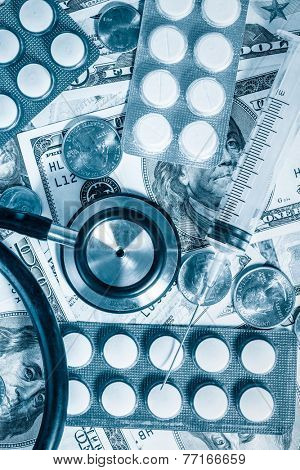 Health care cost - Stethoscope,pills and syringe over a stack of dollars toned in blue