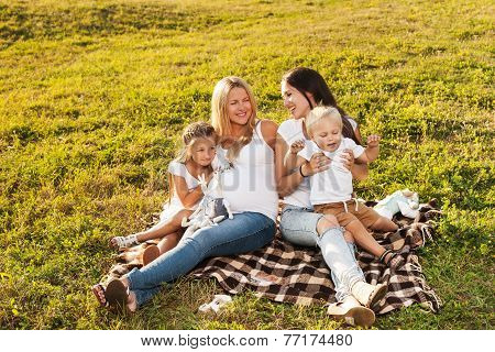 Two Friends With Kids Laughing Outdoors