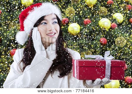 Girl With A Gift Near Christmas Tree