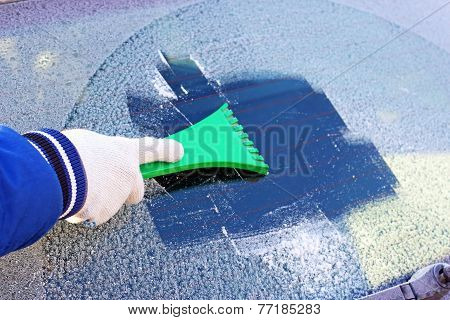 scraping the windshield of a car