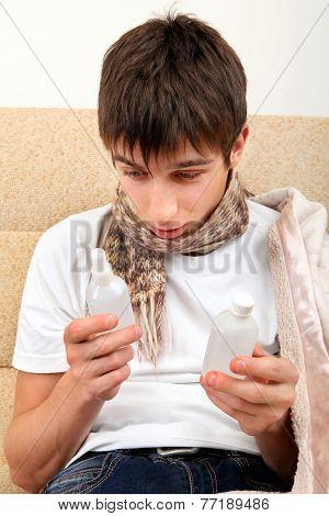 Sick Teenager Looking On Drug Bottles