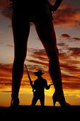 stock photo of redneck  - a silhouette of a woman in her bikini with her cowboy holding weapons in the middle of her legs - JPG