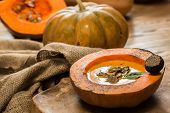 stock photo of hollow  - Cream of pumpkin soup with pumpkin seeds and and garlic croutons  in hollowed - JPG