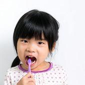 picture of pyjama  - Little Asian girl in pyjamas brushing teeth - JPG