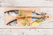pic of peppercorns  - Delicious fresh mackerel fish on wooden kitchen board with lemon rosemary and colorful peppercorns on white textured wooden background - JPG