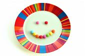 pic of dessert plate  - Smiling face made from candy and colorful plate on white background - JPG