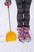 foto of stocking-foot  - winter female feet in boots and patterned tights with a shovel in the snow - JPG