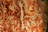 stock photo of aborigines  - Aboriginal artists painted their hand by blowing ochre paint onto their hands through their mouth Many rock paintings are over 3000 years old at Carnarvon Gorge Queensland Australia - JPG