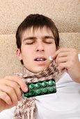 foto of home remedy  - Sick Teenager taking a Pill on the Bed at the Home - JPG