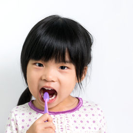 pic of pyjama  - Little Asian girl in pyjamas brushing teeth - JPG