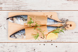 foto of peppercorns  - Delicious fresh mackerel fish on wooden kitchen board with lemon rosemary and colorful peppercorns on white textured wooden background - JPG