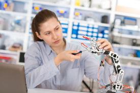 picture of schoolgirl  - schoolgirl adjusts the robot arm model - JPG