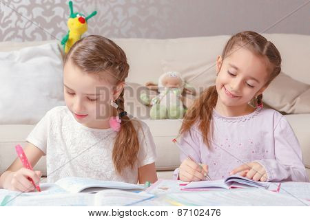 Girls write in note pads