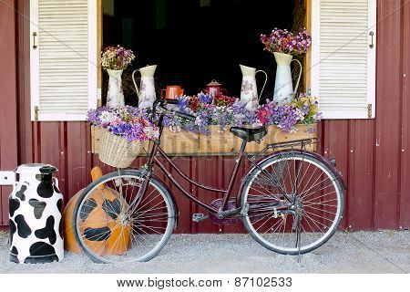 Window Decorated With Flowers In Jugs And Nice Bicycle