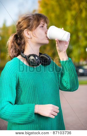 Happy young student girl drinking take away coffee.