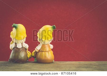 Two Ceramic Doll Sit On Wood