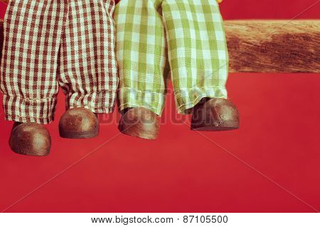 Legs Of Ceramic Doll On Red Background