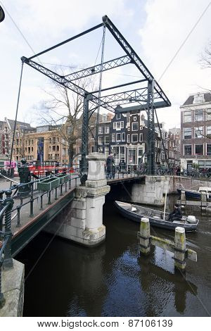 Bridge Over A Canal In Amsterdam With Boat In The Canal
