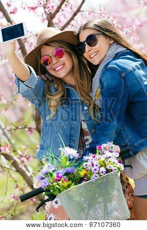 Two Beautiful Young Women Taking A Selfie In The Field.