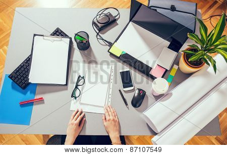Mix of office supplies and gadgets on a wooden desk background