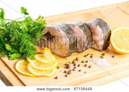 Raw Sliced Steak Of Sturgeon Fish With Greens, Lemon, Different Peppers And Salt, Isolated On White