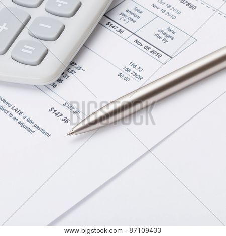 Calculator With Silver Pen And Utility Bill Under It