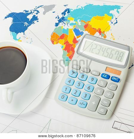 Coffee Cup And Calculator Over World Map