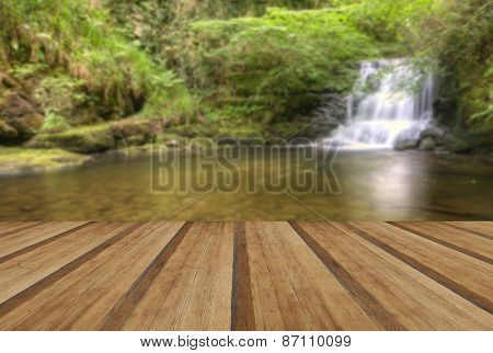 Stunning Waterfall Flowing Over Rocks Through Lush Green Forest With Wooden Planks Floor