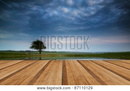 Dramatic Stormy Sky Reflected In Dew Pond Countryside Landscape With Wooden Planks Floor