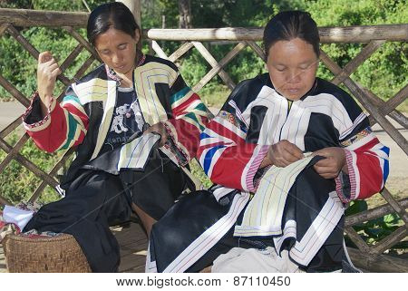 Women of the Black Lahu hill tribe do embroidery work in Mae Hong Son, Thailand.