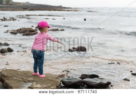 Little Girl Throwing Stones Into The Sea