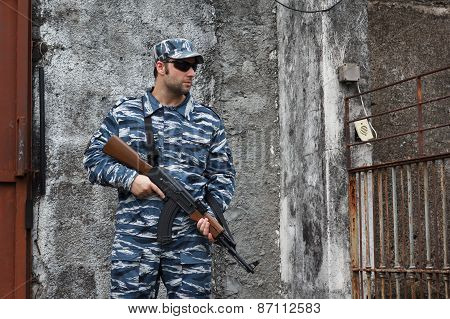 Caucasian Man With Black Sunglasses In Urban Warfare Holding Grifle Near Grade