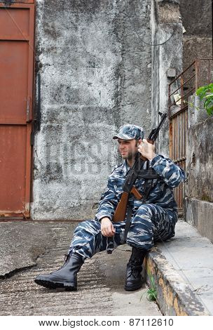 Caucasian Man In Urban Warfare Sitting With Rifle Protecting Gate
