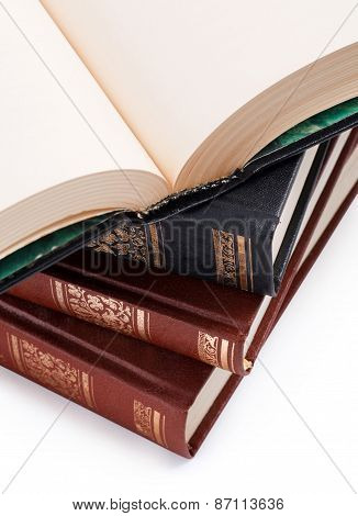 open book with blank pages on a pile of books
