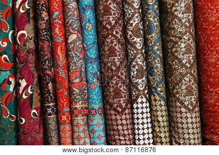 A variety of different bolts of traditional fabric