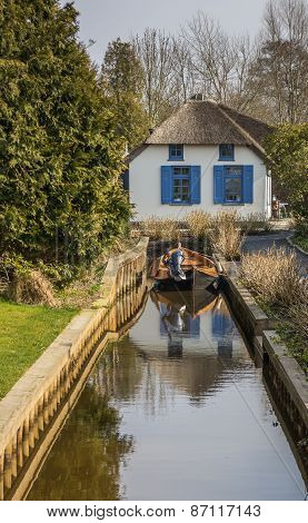 House With Thatched Roof And A Boat In Giethoorn